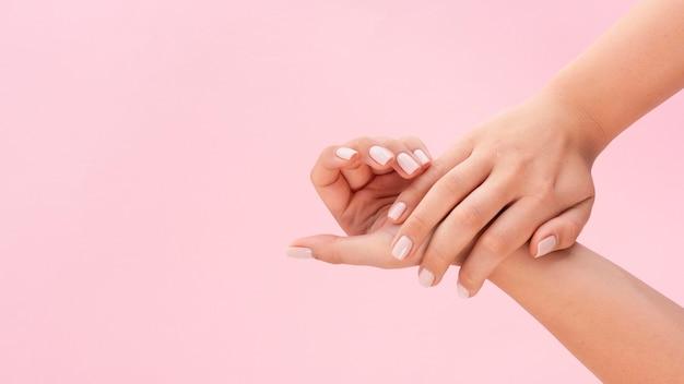 コピースペースとピンクの背景に彼女のマニキュアを示す女性 Premium写真