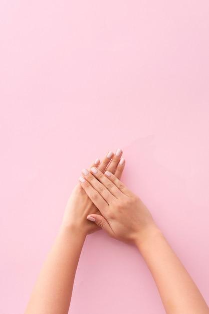 ピンクの背景に彼女のマニキュアを示す女性 Premium写真