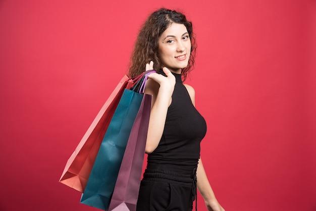 Женщина показывает ее новую одежду покупки на красном фоне. фото высокого качества Бесплатные Фотографии