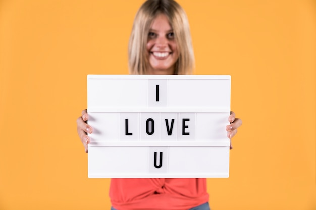 Woman showing i love you text on light box Free Photo