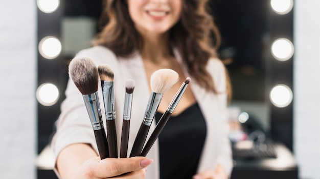 Woman showing makeup brushes on mirror background Free Photo