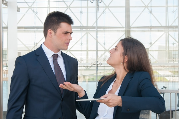 Woman showing man data on tablet, they arguing Free Photo