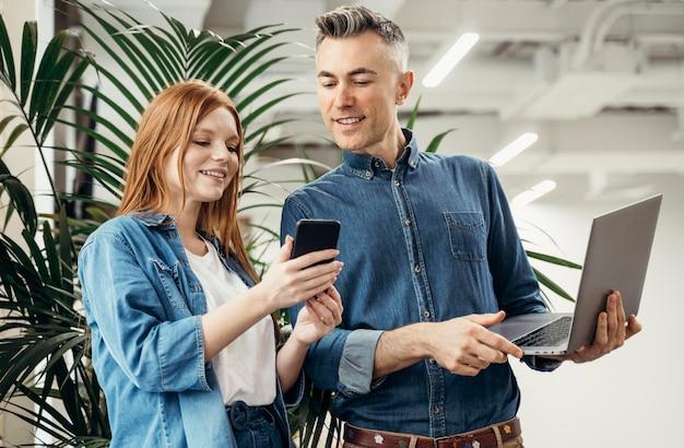 Женщина показывает что-то по телефону своему коллеге Бесплатные Фотографии