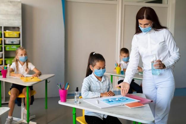 Donna che mostra le precauzioni contro i virus a un bambino Foto Gratuite