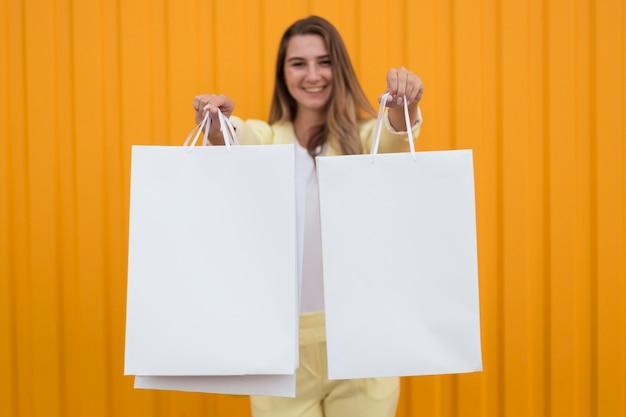 흰색 쇼핑백을 보여주는 여자 무료 사진
