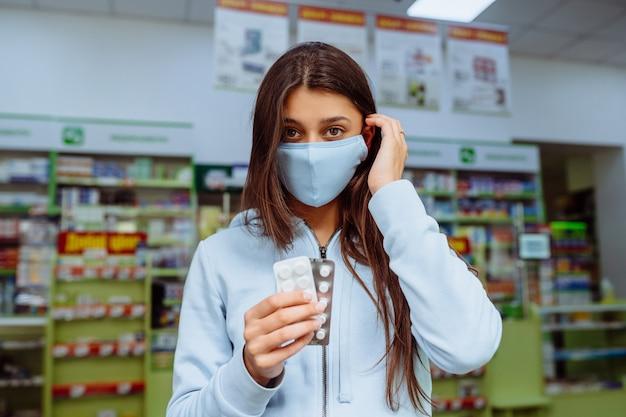 女性は彼の手に丸薬、ビタミンまたは丸薬を示しています。 無料写真