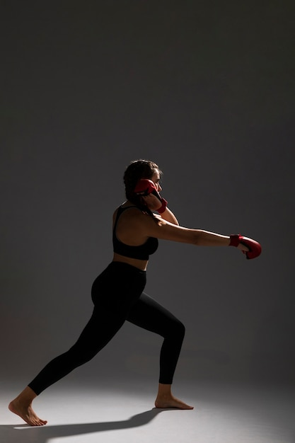 Woman side view punching with box gloves Free Photo
