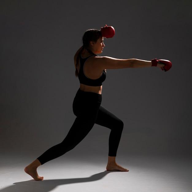 Woman sideways punching with box gloves Free Photo
