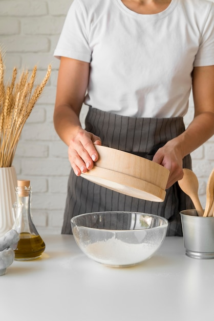 Woman sifting flour over bowl Free Photo