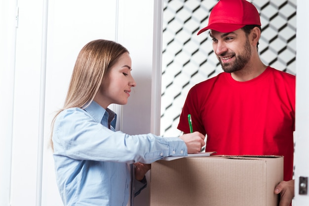 Woman sign the delivery with courier boy in red uniform Free Photo