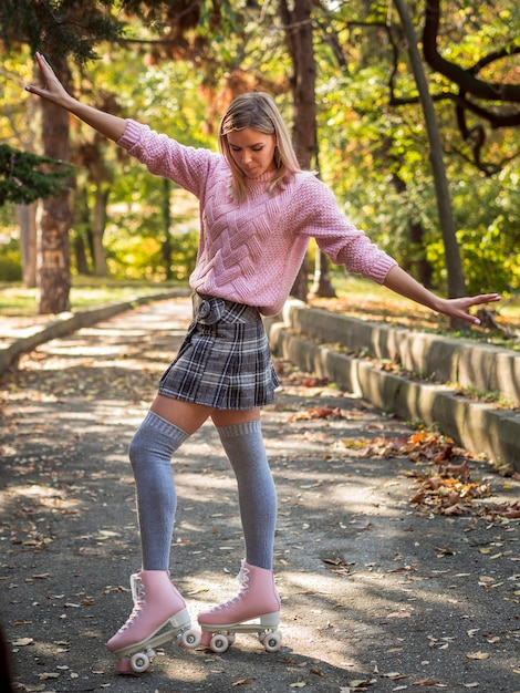 Woman silly posing on street with roller skates Free Photo
