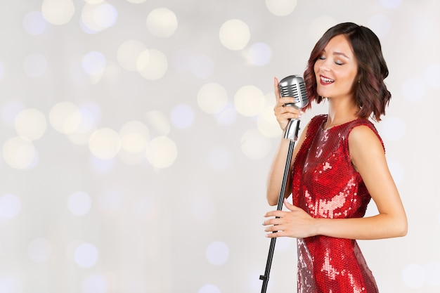 Woman singer in red shiny dress isolated Premium Photo