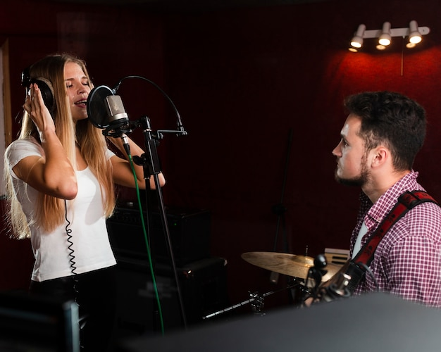 Woman singing in the microphone and guy playing guitar Free Photo