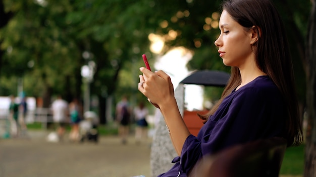 Woman sits on the bench and using smartphone. close view Free Photo