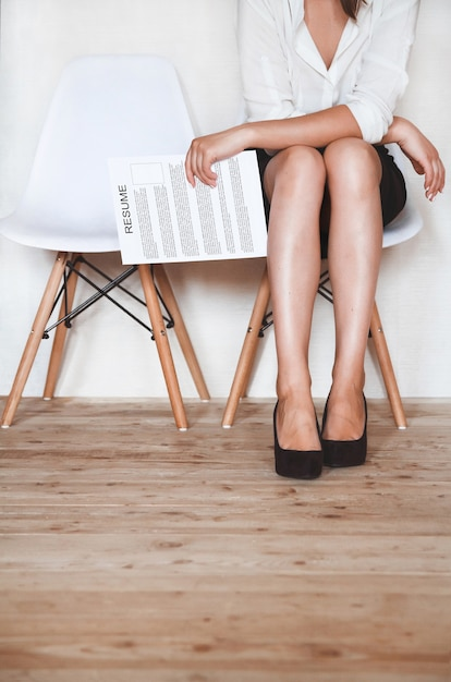 A woman sits in a chair with a resume in hands in anticipation of an interview. Premium Photo