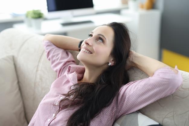 Женщина сидит на диване, скрестив руки за головой, и мечтательно смотрит вверх. Premium Фотографии