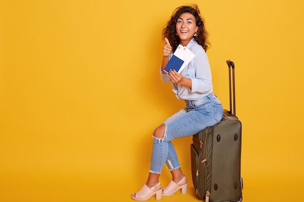 Женщина сидит на сером багаже перед желтым указательным пальцем на билет в руке Бесплатные Фотографии