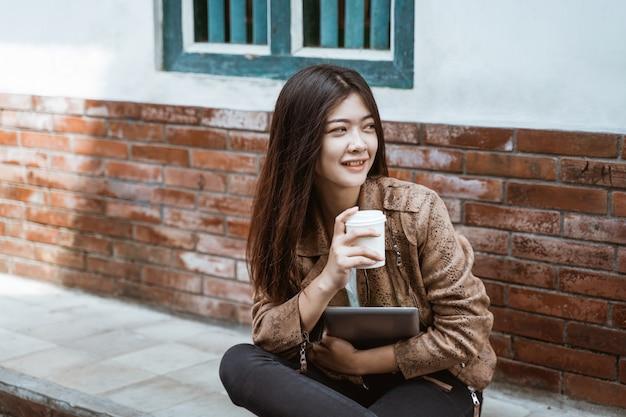 Женщина сидит на обочине дороги, наслаждаясь чашечкой кофе Premium Фотографии