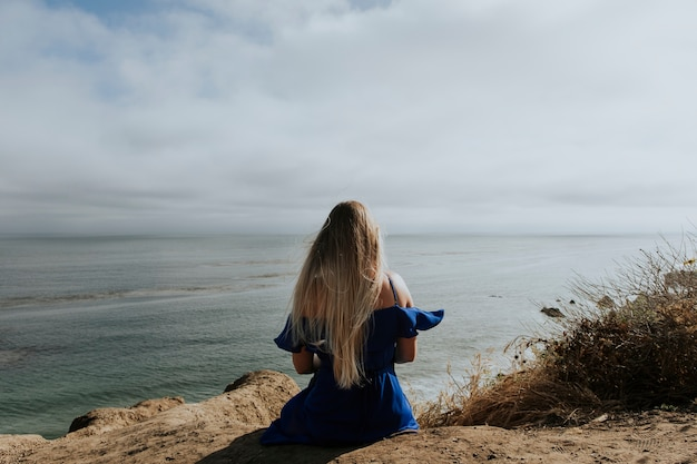 A woman sitting alone at a beach Premium Photo