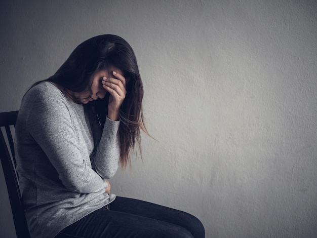 Woman sitting alone in dark room at home. Lonely , sad concept. Premium Photo