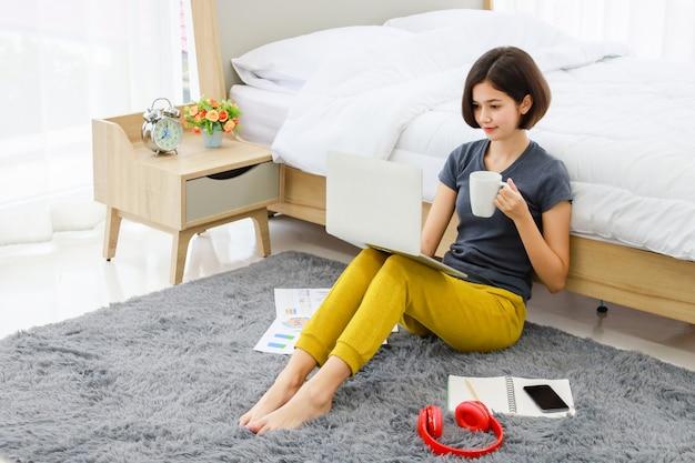 座っていると寝室でコンピューターを使用している女性 Premium写真