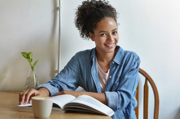 Женщина, сидящая за столом с книгой Бесплатные Фотографии
