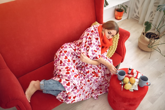 Женщина сидит дома с холодом и пьет горячий чай Бесплатные Фотографии