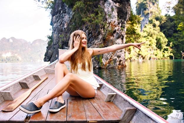伝統的なタイのボートに座っている女性がカオソック国立公園を探索終了 無料写真