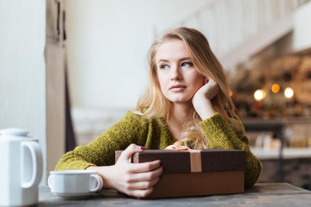 선물 상자와 함께 테이블에 앉아 누군가를 기다리는 여자 프리미엄 사진