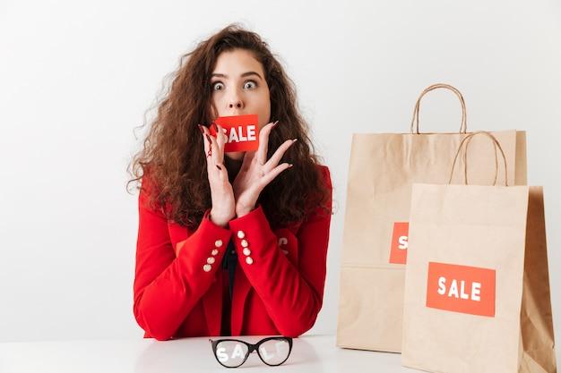 Женщина сидит за столом с бумажными сумками Бесплатные Фотографии