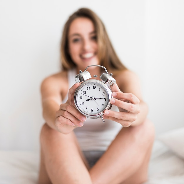 Woman sitting on bed showing alarm clock Free Photo