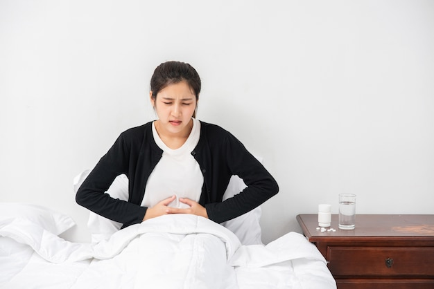 A woman sitting in bed with abdominal pain and pressing her hand on her stomach. Free Photo