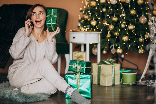 Woman sitting by christmas tree and shopping on the phone Free Photo