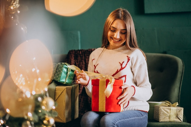 Woman sitting by christmas tree and unpacking christmas present Free Photo