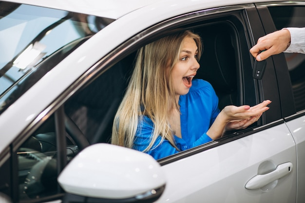 Woman sitting in car and receiving keys in a car showroom Free Photo