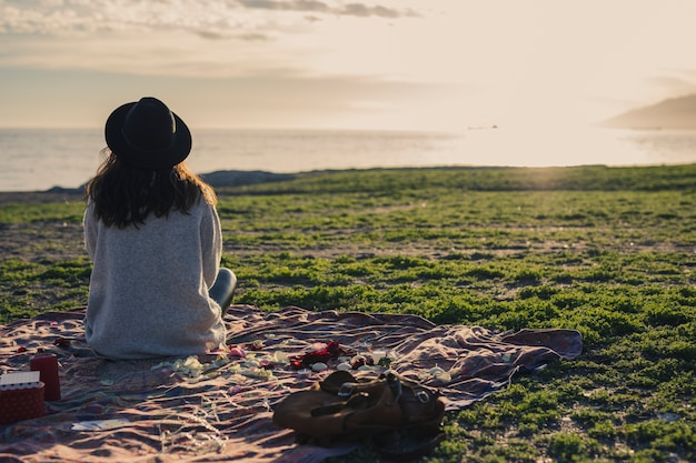 Woman sitting on coverlet on grass Premium Photo