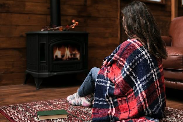 Woman sitting next to fireplace Free Photo