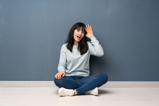 Woman sitting on the floor has just realized something and has intending the solution Premium Photo