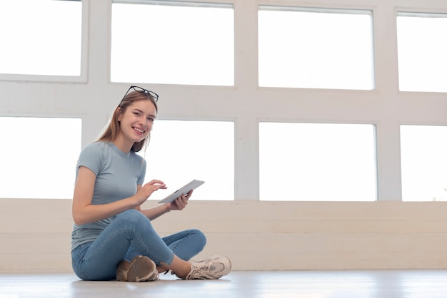Woman sitting on the floor while holding a tablet Free Photo