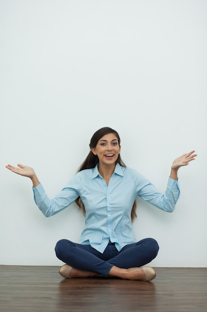 Woman sitting on floor with outstretched hands Free Photo