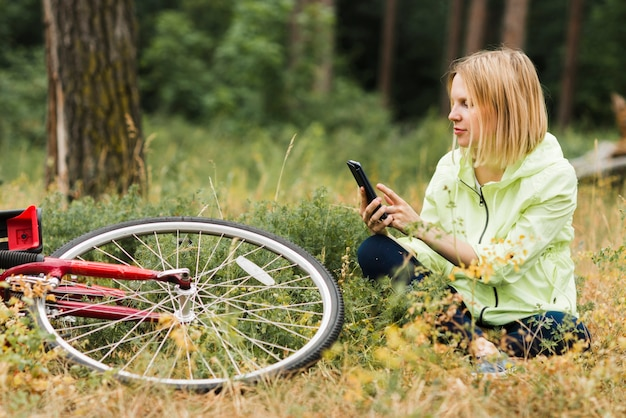 Woman sitting on ground and looking at phone Free Photo