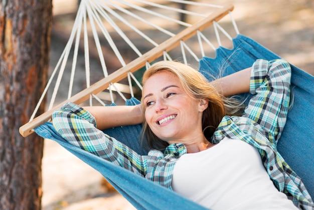 Donna seduta in amaca e guardando lontano Foto Gratuite
