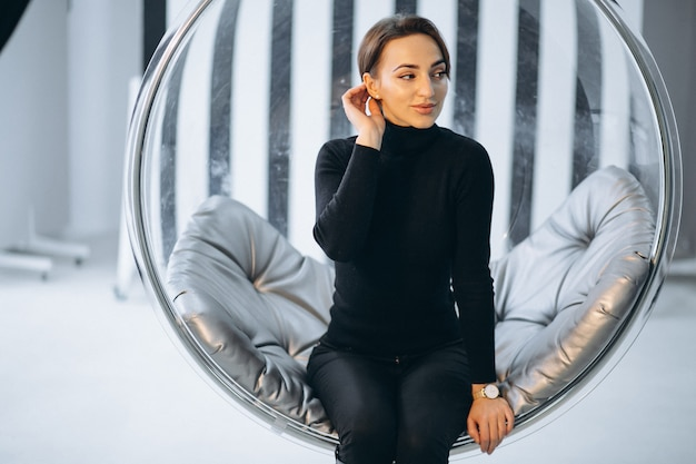 Woman sitting in hanging glass chair Free Photo