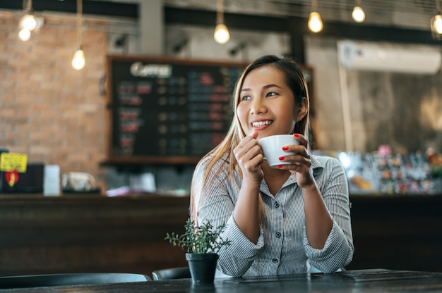 Woman sitting happily drinking coffee in cafe Free Photo