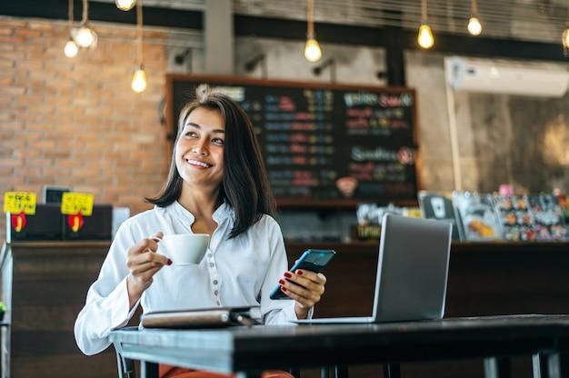 행복 하 게 앉아 커피가 게와 노트북에서 스마트 폰으로 작업하는 여자. 무료 사진