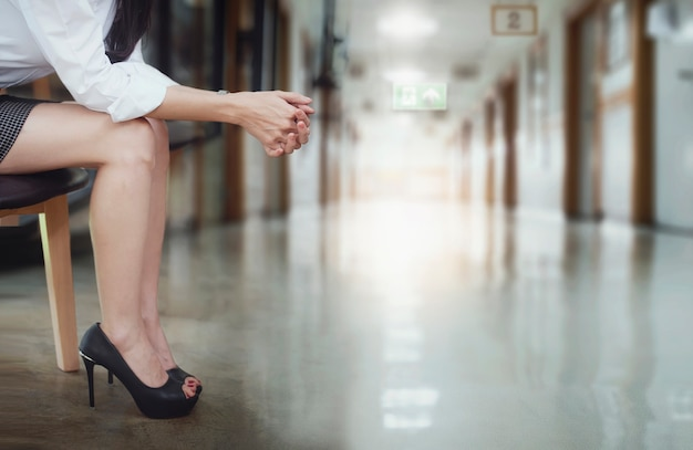 Woman sitting at hospital, holding her hand with stressed while waiting for doctor. Premium Photo
