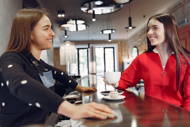 カフェに座っているとバリスタと話している女性 無料写真