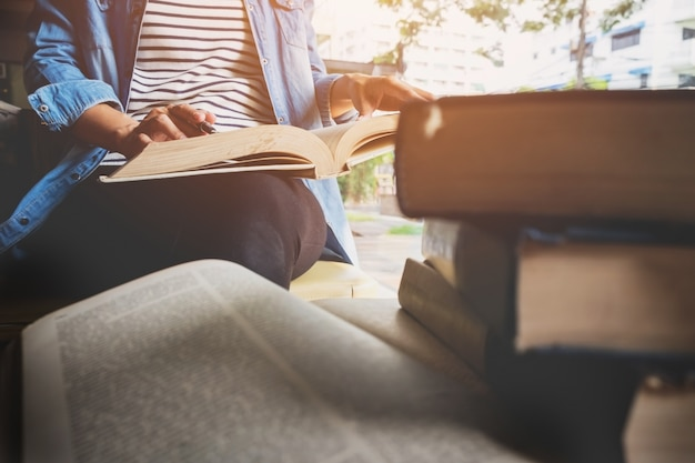 Woman sitting in a cafe, reading book Free Photo