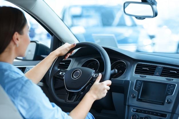 Женщина сидит в новой машине в салоне автомобиля, держа руль Premium Фотографии