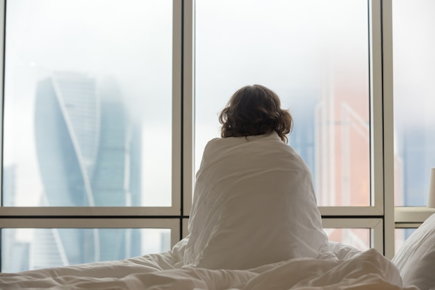 Woman Sitting In Bed Looking Through The Window Photo